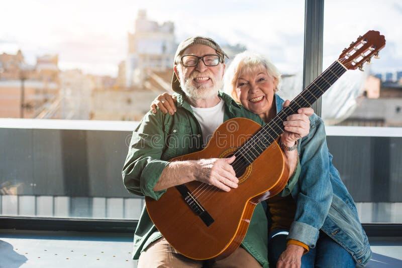 Hoogtepunt van zitting van het het levens de rijpe paar bij venster met gitaar royalty-vrije stock afbeeldingen