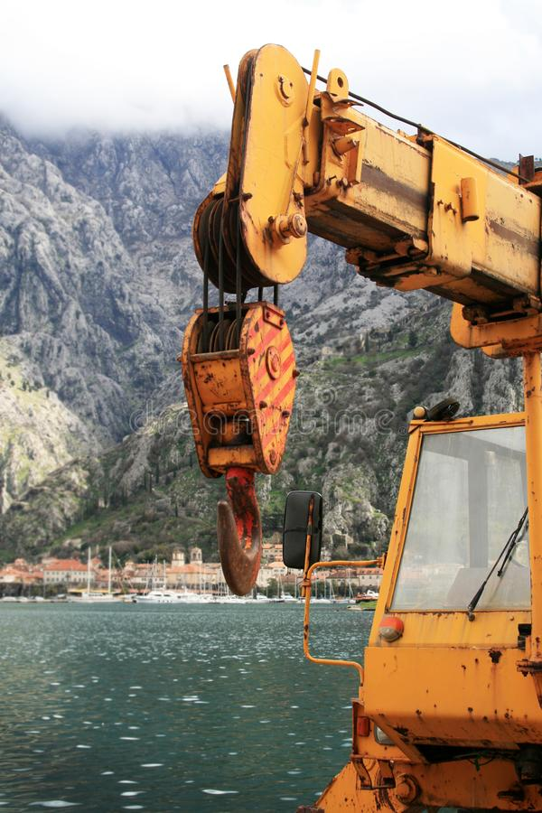 Hook of an old truck-mounted crane hook. Hook and boom on an old truck-mounted crane. In the background is old city of Kotor Montenegro. Photo taken during royalty free stock images