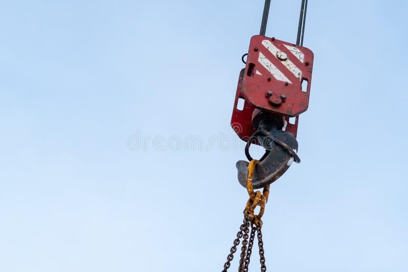 Hook of a construction crane against a blue sky stock photos