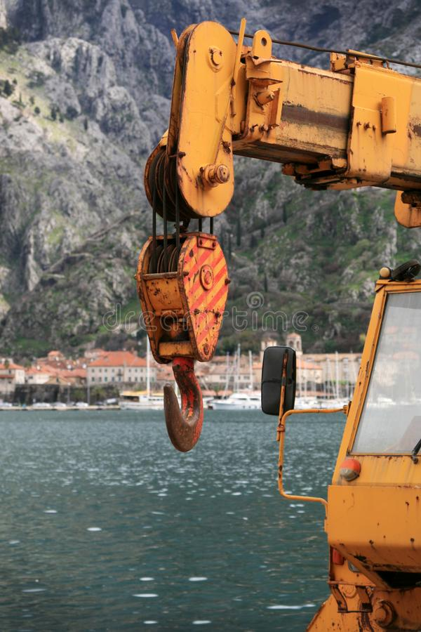 Hook of an old truck-mounted crane. Hook of an truck-mounted crane parked on the working jetty, waiting for operation. In the background is old city of Kotor royalty free stock photography