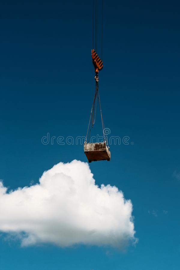 Hook of tower crane and slings. Lifting tower crane during construction of a new building with blue sky and clouds royalty free stock photography