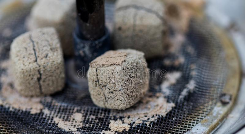Hookah coals in a steel Cup. Smoldering coal in a hookah close-up. Smoke hookah royalty free stock photography