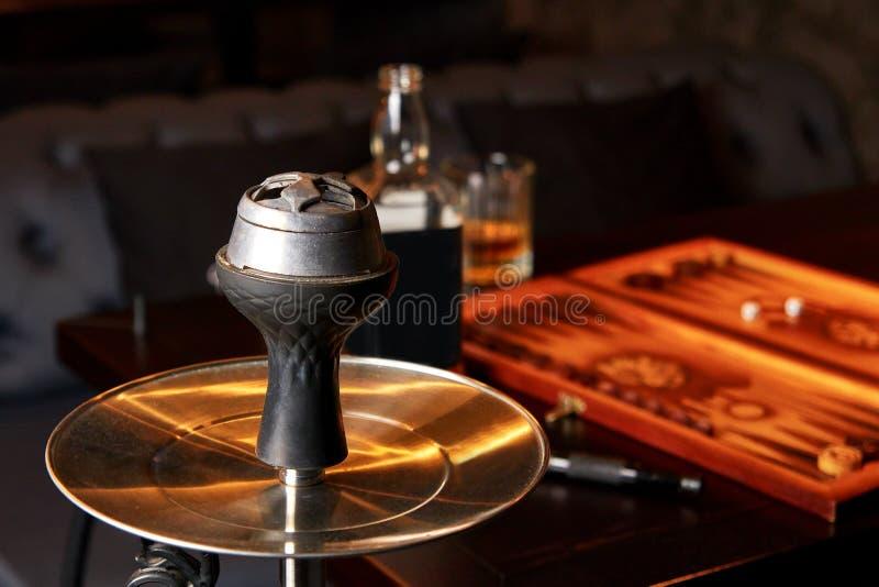 Hookah, flesje en glas whiskey, backgammon-bord op tafel stock fotografie
