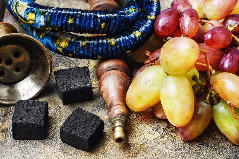 Hookah and grapes. Smoking a hookah pipe,hookah charcoal and grape royalty free stock images