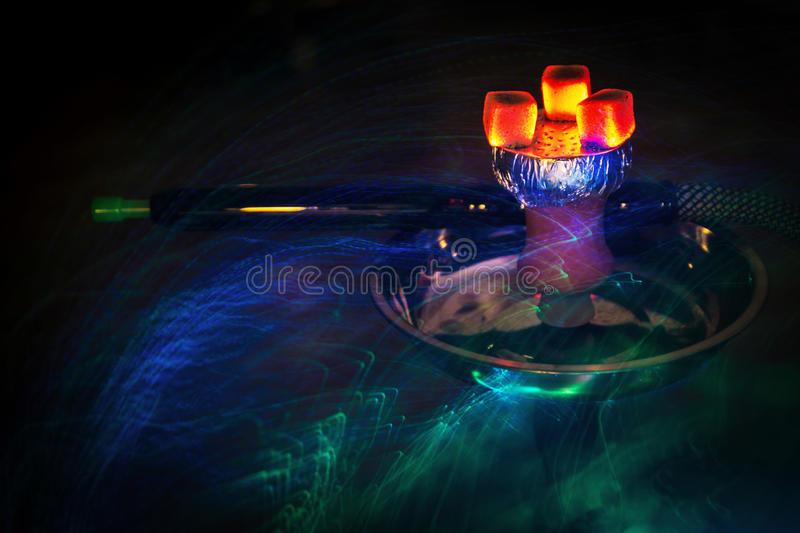 Hookah hot coal. S on shisha bowl with mouthpieces and color lights royalty free stock images