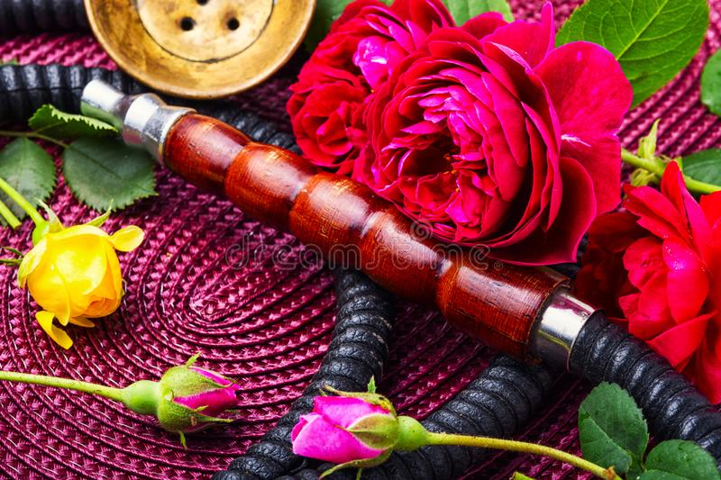 Hookah with rose tobacco. Turkish smoking hookah with the scent of tea rose. Flower tobacco. Smoking. Fashionable shisha stock photo