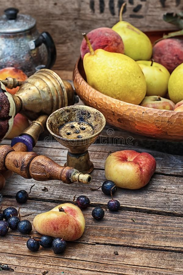 Hookah set mix. Details were worked hookah on the table amid fresh peaches. Photo tinted royalty free stock image