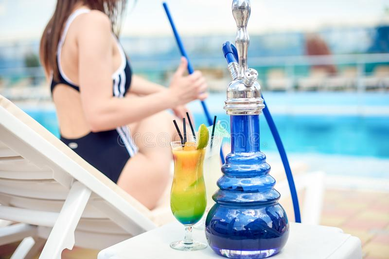 Hookah or shisha or kalian and a tropical summer refreshing alcoholic coctail in front of swimming pool and a beautiful. Woman in bikini or swimsuit. Copy space royalty free stock photography