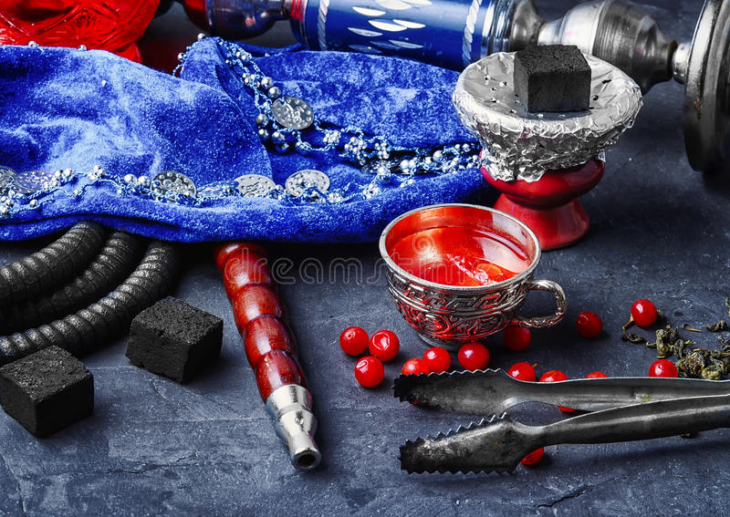 Hookah with tea. Turkish hookah and tea with berries on stone background stock images