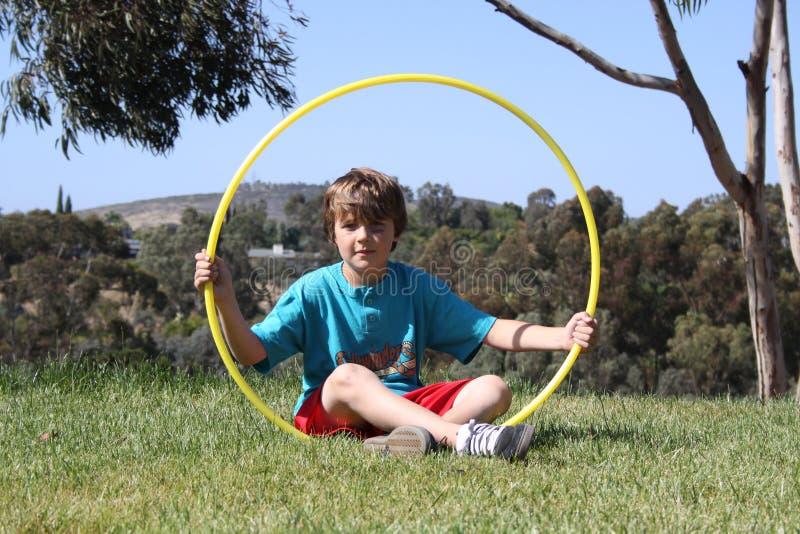 Hoola Circle. Boy sitting on grass holding up a hoola hoop royalty free stock images