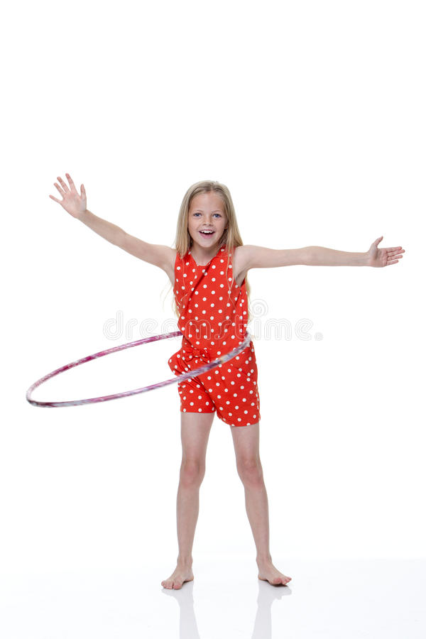 Hoola Hoop. Young girl with plastic hoop around her waist and arms out to her sides with a white background. She is smiling and looking at the camera royalty free stock image
