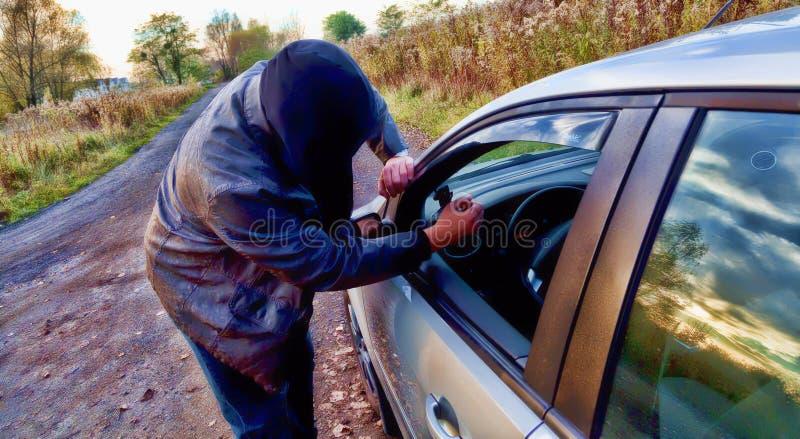 Hooligan die in auto breekt stock foto's