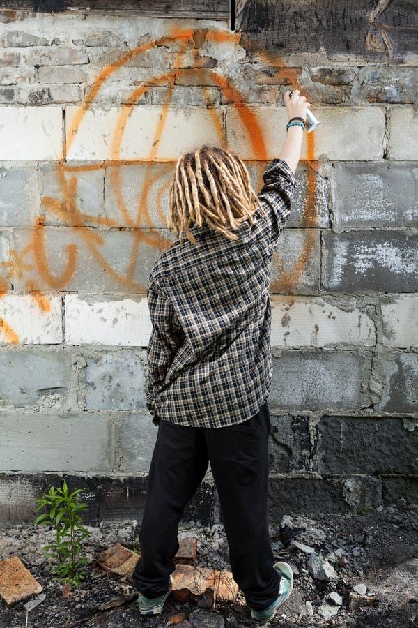 Hooligan het schilderen graffiti op het gebouw stock afbeelding