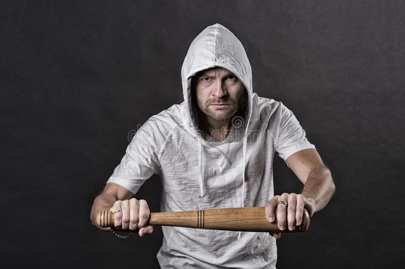 Hooligan hold baseball bat. Bearded man wear hood in hoodie tshirt. Gangster guy threaten with bat weapon. Aggression or royalty free stock image