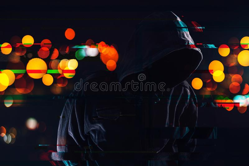 Hooligan with hoodie and obscured face at night stock image