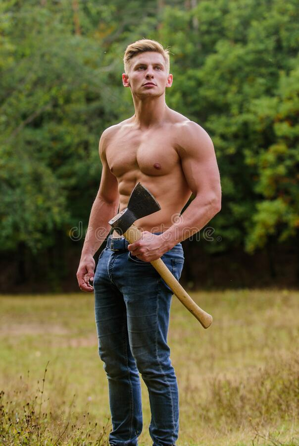 Hooligan man. sexy macho bare torso ax. brutal and attractive male in wood. bodybuilder show his muscles. power and. Strength. lumberjack carry axe. man strong royalty free stock photography