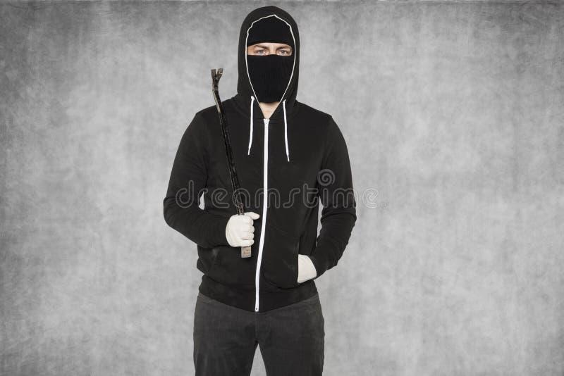 Hooligan met een koevoet op zijn schouder stock fotografie