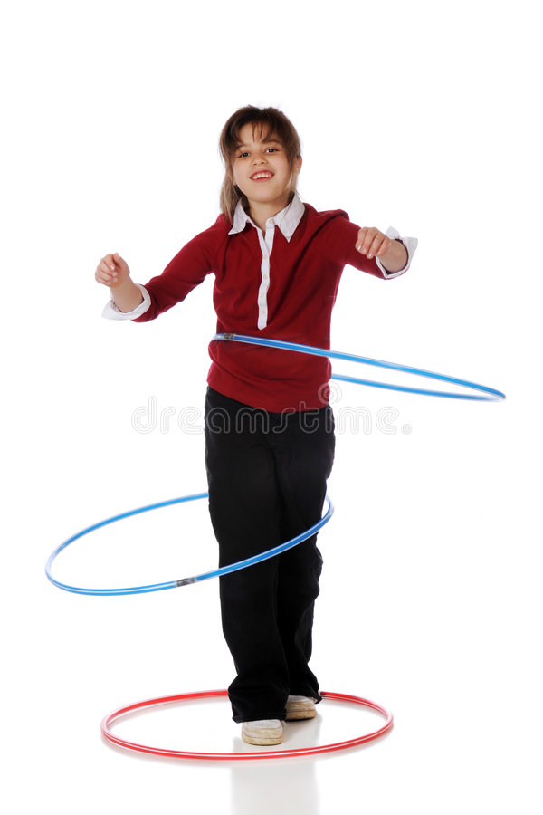 Hoop Practice. A happy elementary girl attempting to spin two hula hoops at a time. One is staying around her waist while the other has slipped around her knees stock photos
