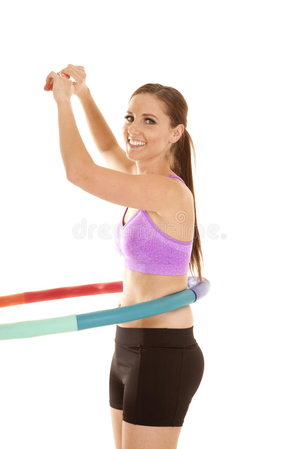 Hoop twist. A woman working out with a weighted hoola hoop stock photos