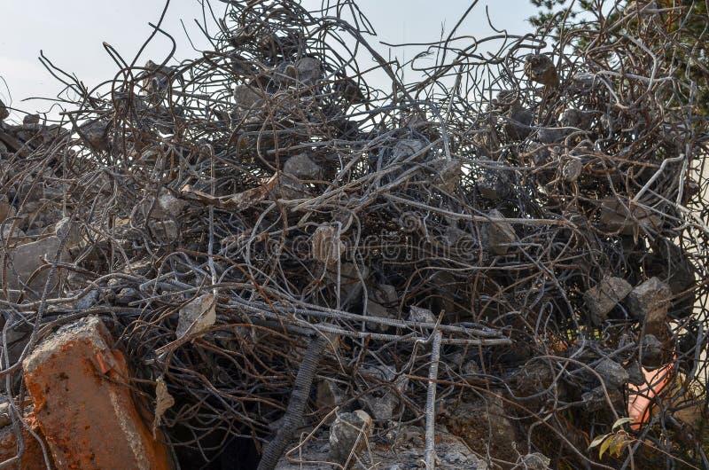 Hoop van bouwpuin: Anker, ijzer om staven, stukken gebroken concrete, gebogen metaalstaven De resten van gebroken stock fotografie