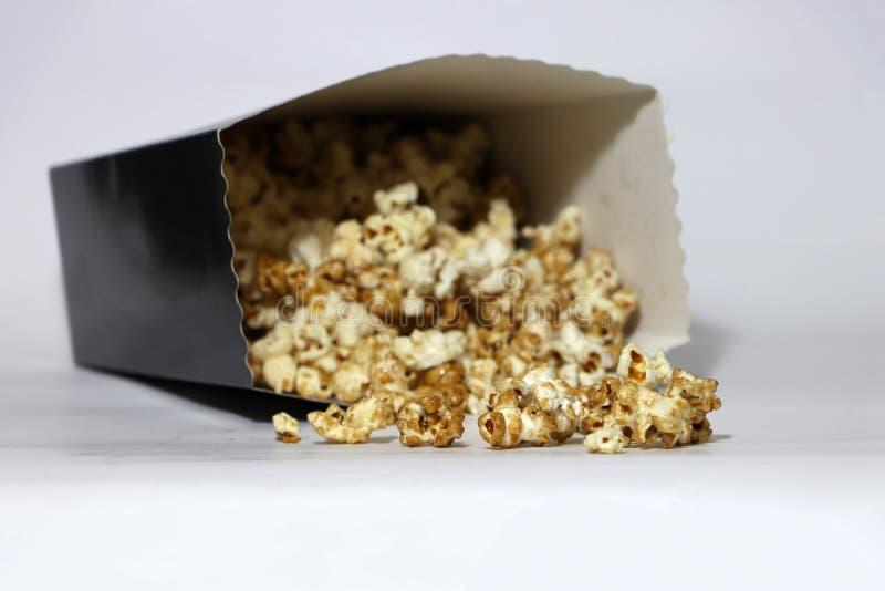 Hoop van chocolade en karamelpopcorn van document vakje op de witte vloer royalty-vrije stock fotografie
