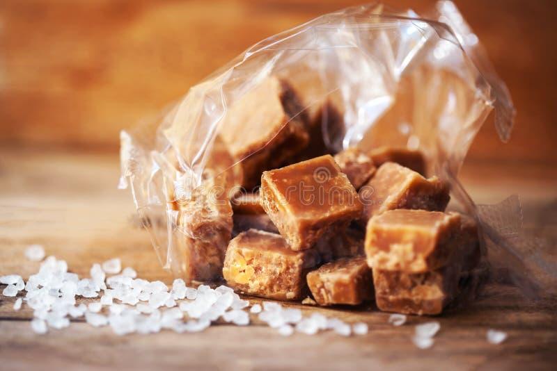 Hoop van Gezouten karamelstukken en overzees zout op een houten lijst Bu royalty-vrije stock foto's