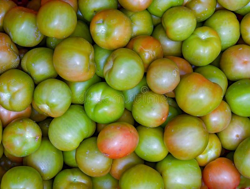 Hoop van groene tomaten in een markt stock afbeelding