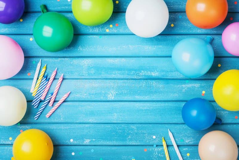 Hoop van kleurrijke ballons, confettien en kaarsen op de turkooise uitstekende mening van de lijstbovenkant De achtergrond van de stock afbeeldingen