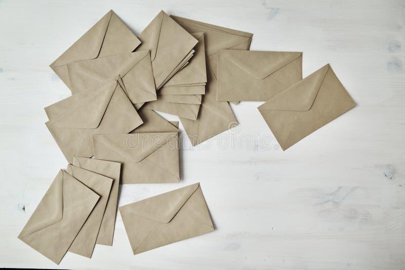Hoop van kraftpapier-document bruine enveloppen op witte houten lijst royalty-vrije stock foto