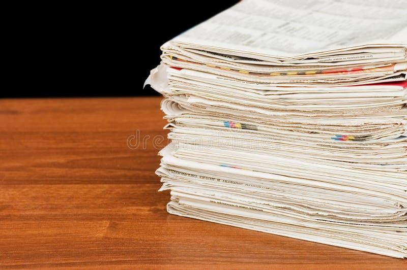 Hoop van kranten op een houten lijst royalty-vrije stock afbeeldingen