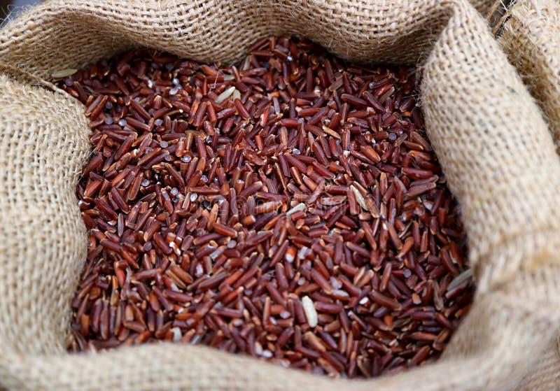 Hoop van Ongekookte Donkerpaarse Kleuren rijst-Bes Rijst in een Natuurlijke Hennepzak stock afbeelding