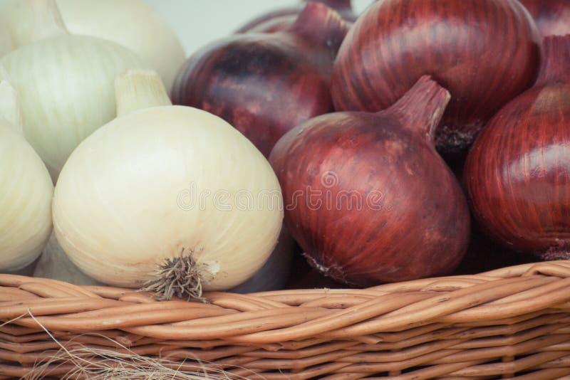 Hoop van rijpe uien in rieten mand, gezonde voeding en plantaardig oogstconcept royalty-vrije stock afbeeldingen