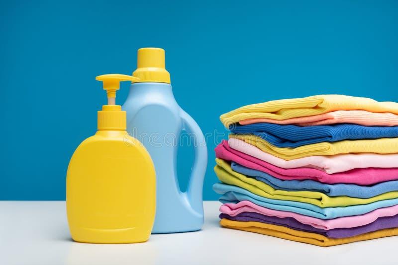 Hoop van schone die kleren dichtbij detergentia worden gevouwen stock foto