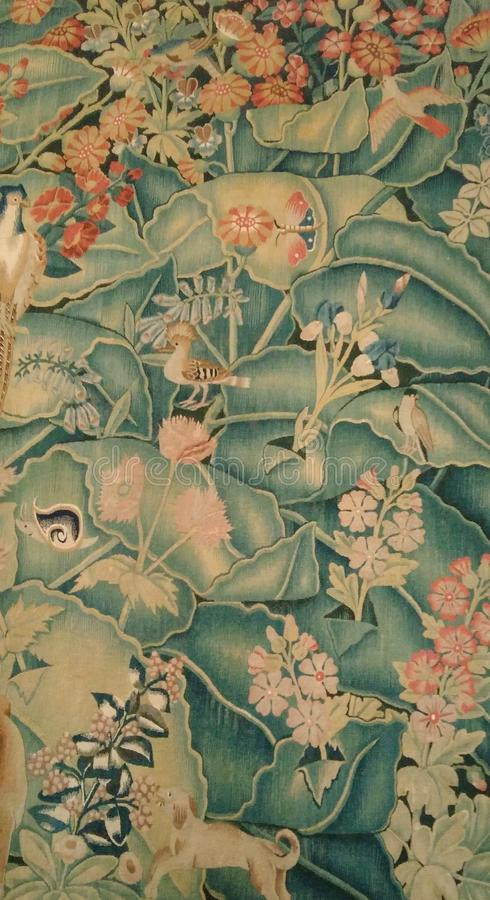 A hoopoe Upupa epops on a tapestry. A hoopoe Upupa epops in green canopy on an old tapestry surrounded by flowers and other animals royalty free stock images