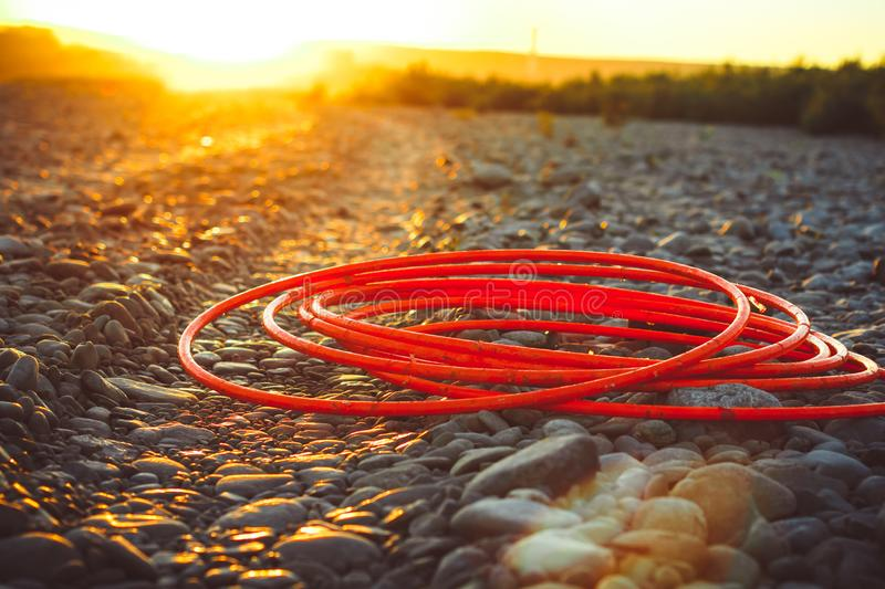 Hoops are lying. Hula hoops lie in on the rocks in the sunset rays royalty free stock images