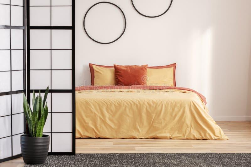 Hoops pretos em uma parede branca no quarto com camas laranja na cama foto de stock