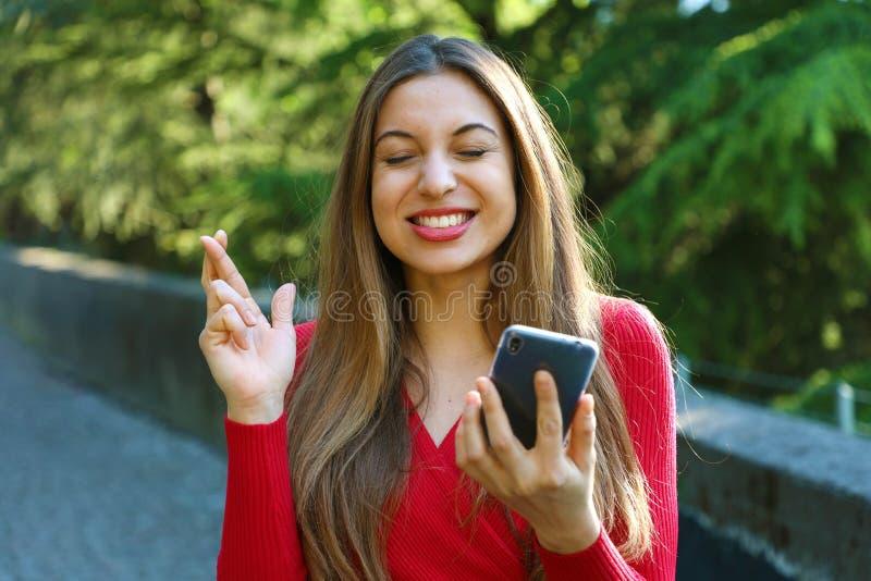 Hoopvol meisje die vingers kruisen die een smartphone houden wachtend op nieuws openlucht Jonge vrouw met de kruising van vingers royalty-vrije stock foto