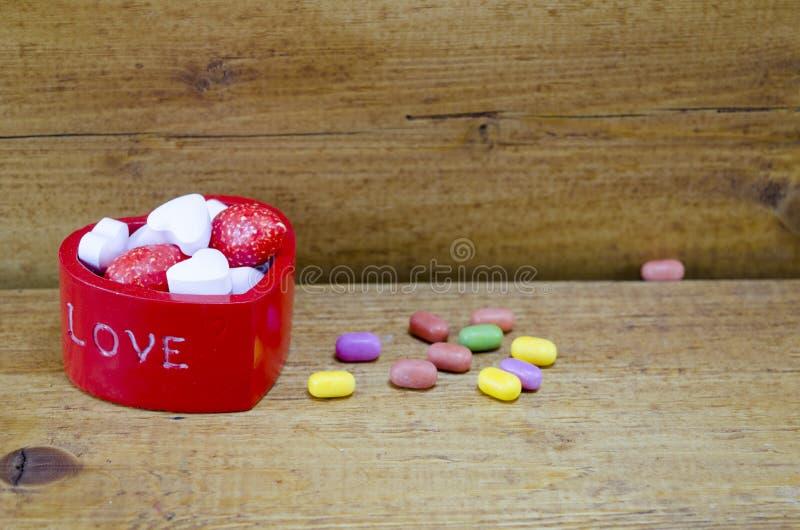 Hoor gevormde die doos met kleurrijk suikergoed wordt gevuld stock afbeeldingen