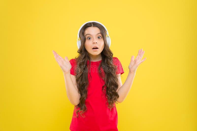 Hoor het en leef het Aanbiddelijke hoofdtelefoongebruiker op gele achtergrond Klein kind die regelbare witte hoofdtelefoon dragen stock foto's