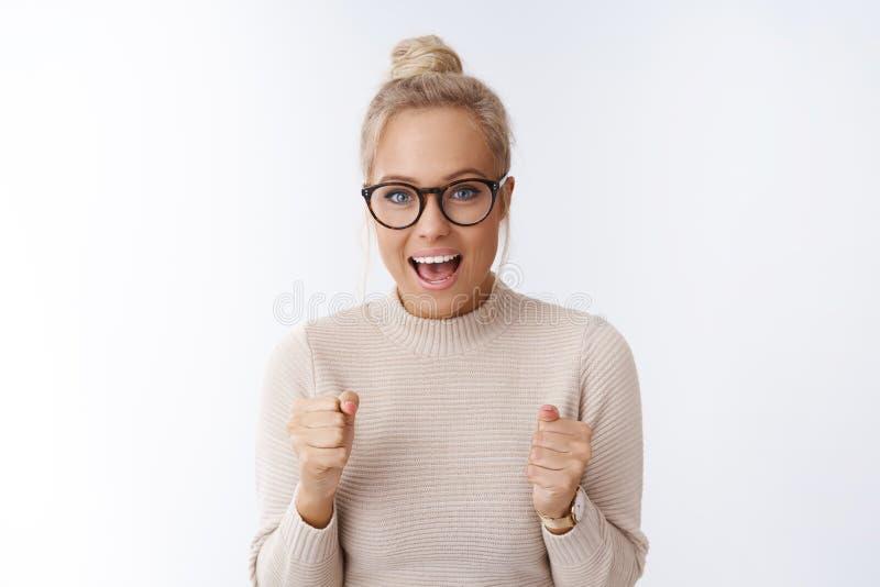 Hooray dumny ty Entuzjastycznej odświętności śliczna blond kobieta zaciska pięści od szczęścia i radości tryumfuje w szkłach, zdjęcia stock