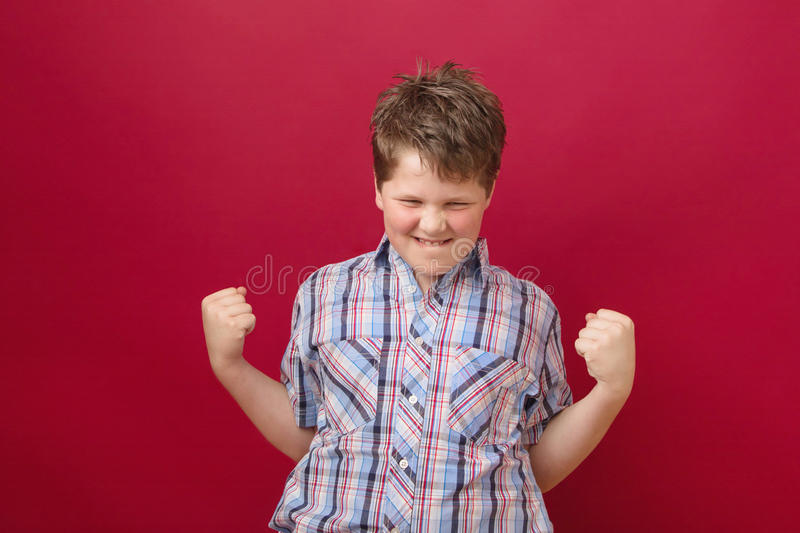 Hooray - finally managed - boy with power. Hooray - finally managed. Lucky boy on red background royalty free stock image