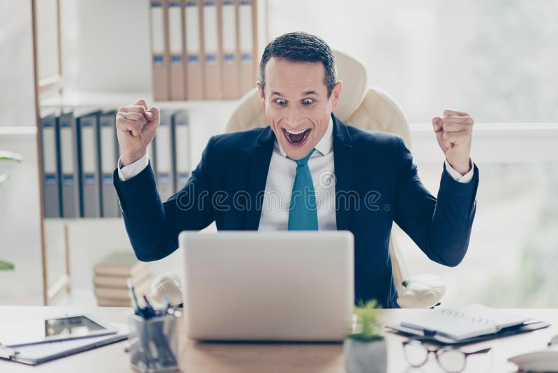 Hooray I did it! Excited cheerful joyful funny financier in raising hands up in front of laptop sitting in luxurious fashionable. Light office royalty free stock photography