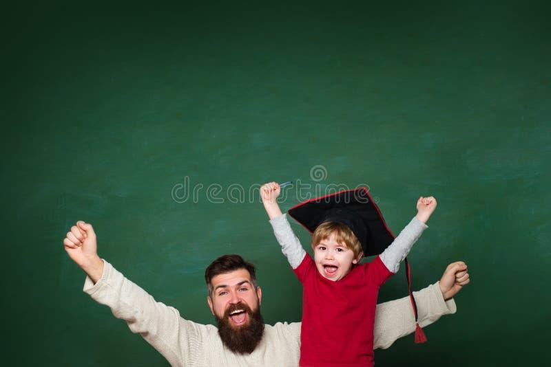 hooray Vader die haar zoon in klaslokaal onderwijzen op school Twee generaties Jonge jongen die zijn schoolthuiswerk met van hem  royalty-vrije stock foto