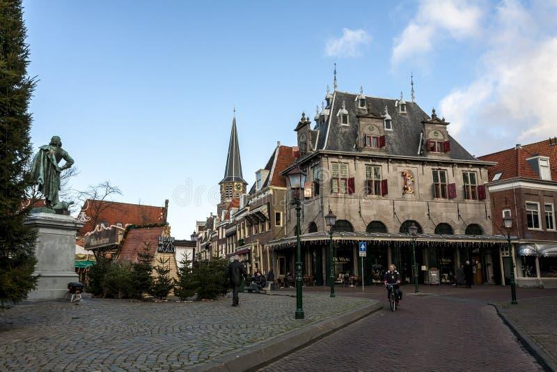 Hoorn Nederländerna - December 11, 2009: Fyrkanten Roode Steen med väger huset De Waag Folk som utanför sitter och dricker royaltyfria foton