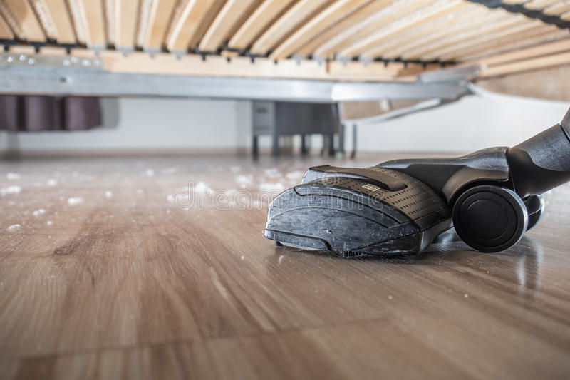 Hoovering the sust on the wood floor. Dust and dirt dirt under the bed royalty free stock photography
