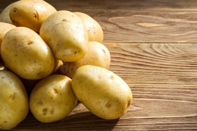 Hop van hele gele aardappelen in het zonlicht op een bruine houten tafel Groenten, vegetariër en gezond eten Voedingsingrediënten royalty-vrije stock foto's