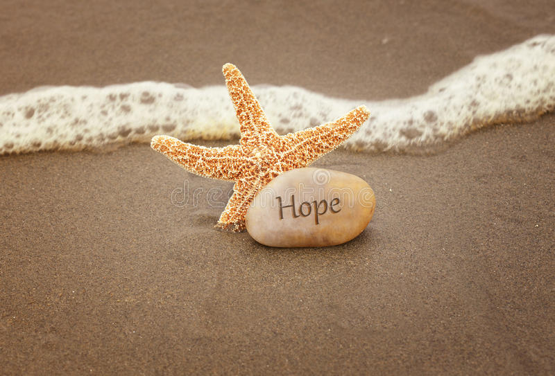 Hope. Calming image of hope. Starfish and a rock by the ocean waves