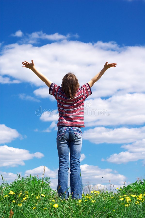 Hope. Girl holding arms up in praise against blue sky