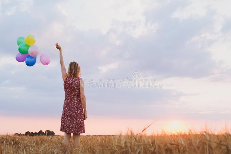Hope concept, emotions and feelings, woman with colourful balloons. In the field, background royalty free stock photo