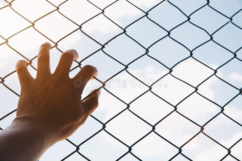 Hope concept,unhappy man hand sad hopeless at fence prison in jail, no free and freedom struggle teen concept stock photos